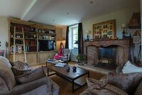 Sofas and coffee table in front of traditional open fireplace in rustic living room