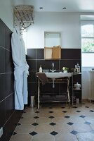 Bathroom with washstand against black-tiled wall and vintage-style towel rack with white dressing gowns hung on hooks
