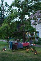 Romantic candlelit atmosphere around set garden table in rustic setting
