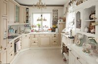 Fitted kitchen with cream fronts, jumble of ornaments on white dresser and utensils in colour-coordinated pastel shades