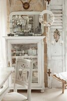 White chair and table in front of display cabinet in shabby-chic interior