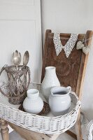 China and wicker vessels on white-painted wicker tray and old wooden chair decorated with lace collar