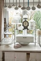 Enamel ladles hanging from ceiling above cake stand, bread basket and kitchen scales in vintage. shabby-chic interior