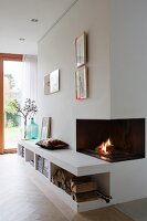 Fire in open fireplace and low sideboard integrated into wall