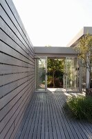 Wooden terrace with garden shower in front of glazed corridor