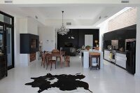 Open-plan designer kitchen with fireplace and animal-skin rug on white floor