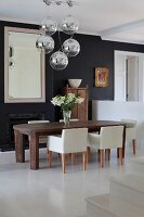 Pale designer chairs around solid wooden table below spherical chrome pendant lamps in front of black-painted wall