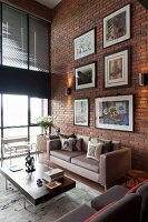 Gallery of artworks on brick wall of loft living room with retro furniture and glass wall