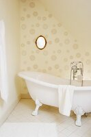 Free-standing, clawfoot bathtub with vintage tap fittings in front of oval mirror on wall with circle-patterned wallpaper