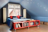 Low, red sideboard on castors at foot of bed and standard lamps against gable end wall in attic room painted mid blue