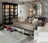 Classic living room in shades of grey with plexiglas coffee table and black display cabinet