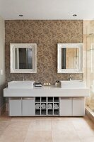 Twin washstand with square basins in elegant bathroom with ornamental wallpaper