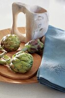 Artichokes, blue linen napkins and jug on wooden dish