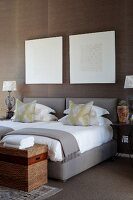 Graphic art above twin beds with grey upholstered frames, elegant scatter cushions and trunk at foot