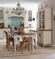 Country-house-style kitchen-dining room with dining set on rug