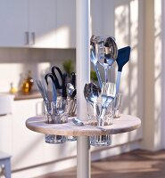 Round minibar with cutlery holders on telescopic pole in kitchen