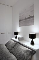 Grey patterned bed linen on bed, black table lamps on shelf and black and white photo of sailing boats