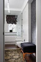 Antique ottoman with black velvet cover and rug on tiled floor in comfortable bathroom with modern ambiance