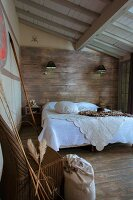 White bedspread on double bed below sconce lamps on wood-clad wall in rustic bedroom