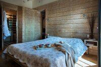 Breakfast tray on double bed with bedspread in rustic bedroom with horizontal wooden cladding