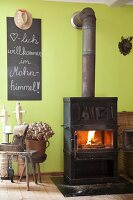 Iron kitchen stove, dried poppy seedheads and welcome message on blackboard on green wall