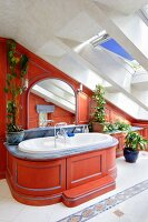 Custom bathtub installation with curved wooden surround painted red below skylights