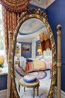 Oval cheval mirror with carved frame reflecting antique footstool and luxurious double bed with half-tester canopy