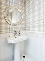 Oval mirror above pedestal sink and pale tartan wallpaper above white wainscoting