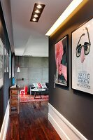 Narrow hallway with posters on black wall and view into lounge area with concrete wall
