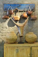 Faux animal skull amongst woven vessels on pale wooden cabinet below hand-crafted cow bells hanging from hooks on clay wall