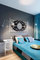 Grey and white bedroom with sky blue textiles and ethnic accents