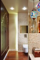 Colourful spherical lamps above washstand with pebble mosaic in front of partitioned toilet area with indirect lighting and fitted cupboards to one side