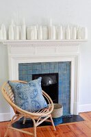 Bent bamboo easy chair with blue patterned cushion in front of fireplace; collection of white bottles on mantelpiece
