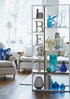 Decorative letters and glass and ceramic vases on free-standing shelves