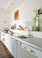 Modern kitchen counter with pale grey worksurface, kitchen utensils on shelf against wall
