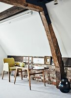 60s table and chair against brick knee wall in converted attic with original old roof beams