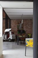 Dining area and bubble car against brick wall in loft apartment