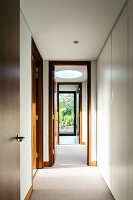 Narrow corridor with wooden interior doors, round skylight and white, fitted cupboards along one side