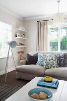 Grey sofa with scatter cushions & tripod, studio-style standard lamp in modern living room