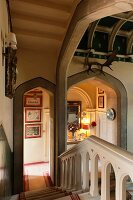 View down staircase in Jacobean manor house with Tudor arches