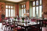 Festively set table in grand dining room with red and gold patterned wallpaper and wood-panelled window reveals