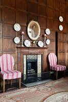 Open fireplace flanked by white and pink striped chairs, decorative china wall plates on wood-panelled wall and hand-made Aubusson-style rug