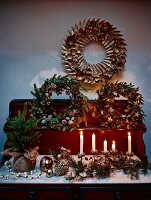 Various, artistically arranged wreaths of leaves, candles and Christmas decorations on chest of drawers with shelf unit on top
