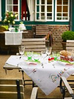 An embroidered tablecloth on a garden table with lots of wine glasses on a terrace