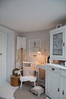 White dresser next to cosy seating area with romantic ambiance