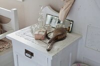 Hairbrush, hand mirror and various crystal bottles and jars on white-painted bedside cabinet