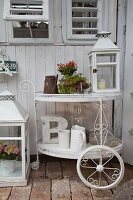 White-painted vintage tea trolley decorated with lantern, potted plants and white jugs