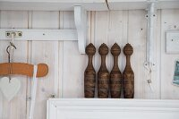Old wooden skittles on narrow shelf against wooden wall stained white