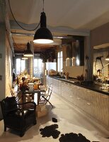 Kitchen counter along entire wall and dining area below row of vintage pendant lamps in open-plan interior