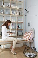 A woman reading on an upholstered bench with a cushion hanging on the wall from hooks in front of a light painted designer shelf system
